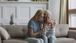 Worried young daughter consoling sad crying old senior mother