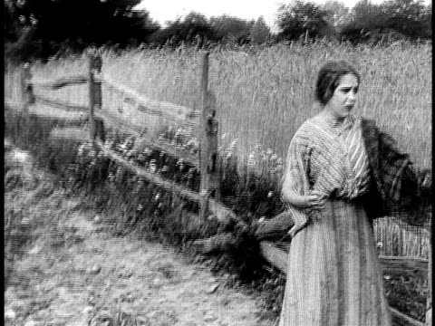 1910 b&w worried young woman at wooden fence, dropping bundle and walking away with arms extended/ usa - 1910 stock-videos und b-roll-filmmaterial