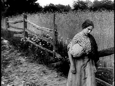 1910 b&w worried young woman leaning against wooden fence/ usa - anno 1910 video stock e b–roll