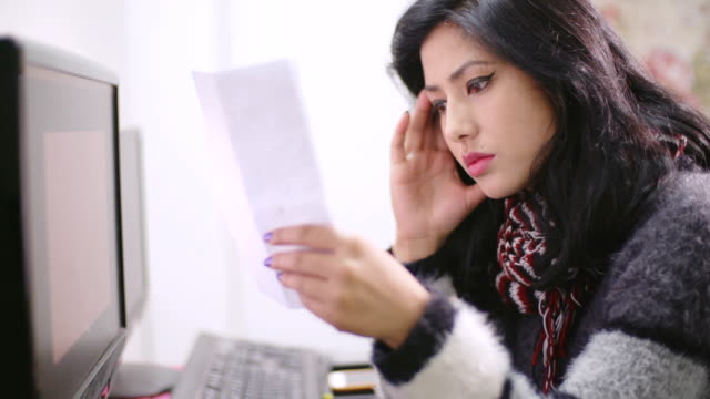 worried young woman paying bills on computer. - debt stock videos & royalty-free footage