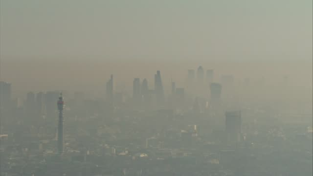 worries over air quality trigger pollution alerts across the country air view smog clouds around city of london skyscrapers - trigger stock videos & royalty-free footage