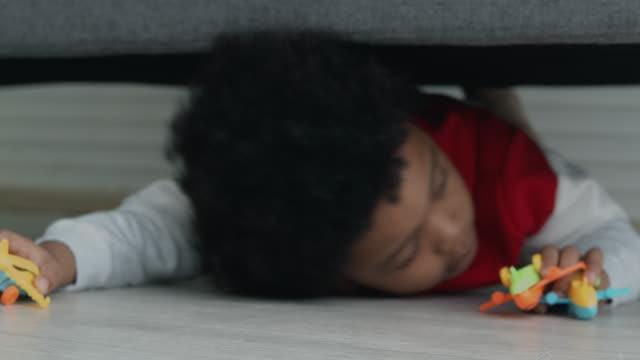 vídeos de stock, filmes e b-roll de criança preocupada tente se esconder debaixo do sofá. - esconder