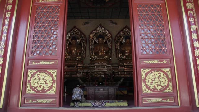A worshiper kneels in a Chinese temple.
