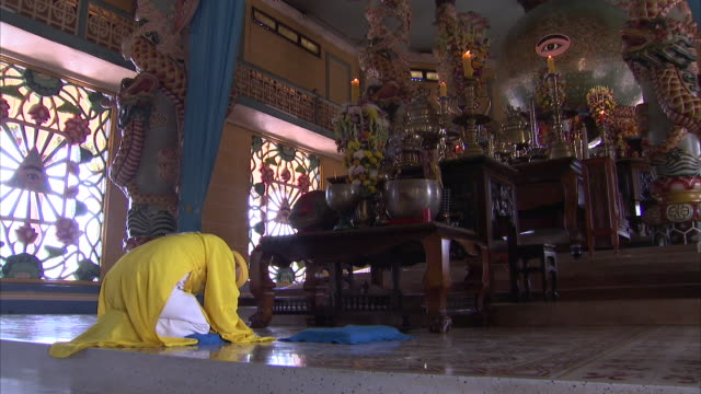 a worshiper kneels in the cao dai temple in vietnam. - tay ninh stock videos & royalty-free footage