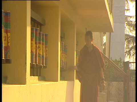 stockvideo's en b-roll-footage met a worshiper walks past prayer wheels and spins them - gelovige