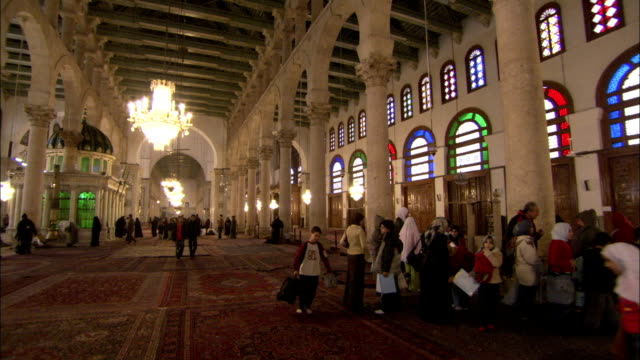 Worshipers and tourists walk around the interior of the Umayyad Mosque. Available in HD.