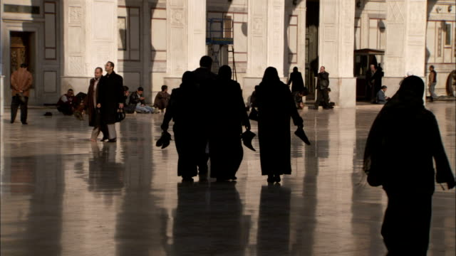 Worshipers carry their shoes through the central courtyard of the Umayyad Mosque Damascus. Available in HD.