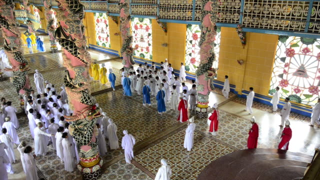 worshipers in colorful robes gather for prayer in the cao dai temple in tay ninh, vietnam. - tay ninh stock videos & royalty-free footage