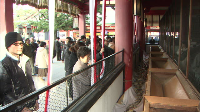 worshipers kneel and ring bells at a shrine on new year's day. - shrine stock videos and b-roll footage