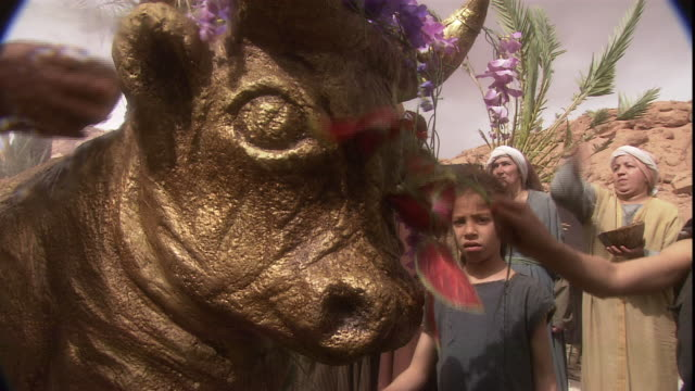 worshipers pay tribute to a statue of a golden bull in a biblical reenactment. - praying stock videos & royalty-free footage