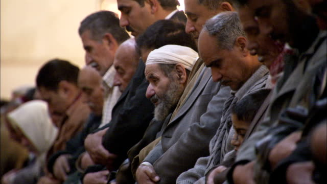 Worshipers stand in prayer in the Umayyad Mosque Damascus. Available in HD.