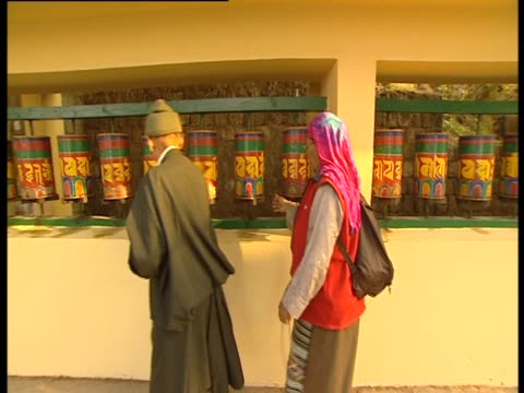 stockvideo's en b-roll-footage met worshipers walk past prayer wheels and spin them - gelovige