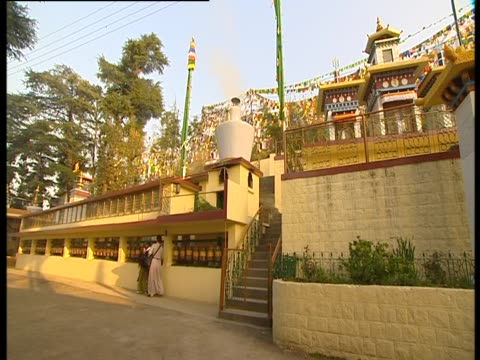 stockvideo's en b-roll-footage met worshipers walk past prayer wheels below temple - gelovige