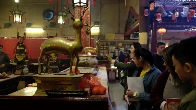 vídeos y material grabado en eventos de stock de a worshipper prays and offers incense at the man mo temple in hong kong china on wednesday feb 14 2018 a worshipper lights incense sticks at the man... - sheung wan