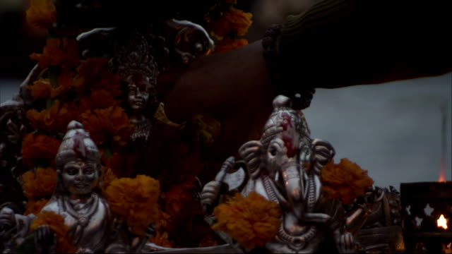 A worshipper puts petals near a silver Ganesh statue Ganga Aarti festival. Available in HD.