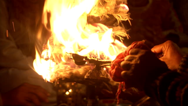 A worshipper sets fire to a candelabra at the Ganga Aarti Haridwar festival. Available in HD.