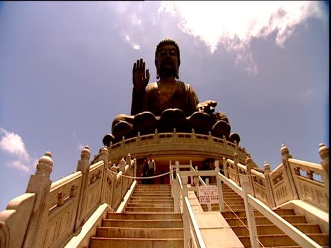 worshippers and tourists milling around base of huge buddha statue lantau island - lantau stock videos and b-roll footage