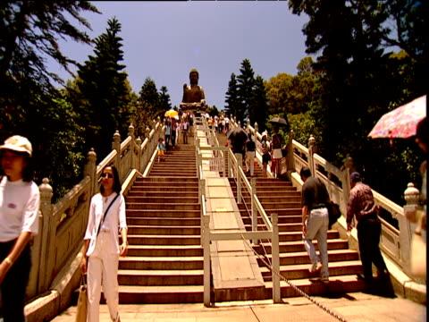 worshippers and tourists on steps up to huge buddha statue lantau island - lantau stock videos and b-roll footage