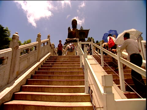 worshippers and tourists on steps up to huge buddha statue lantau island - wallfahrt stock-videos und b-roll-filmmaterial