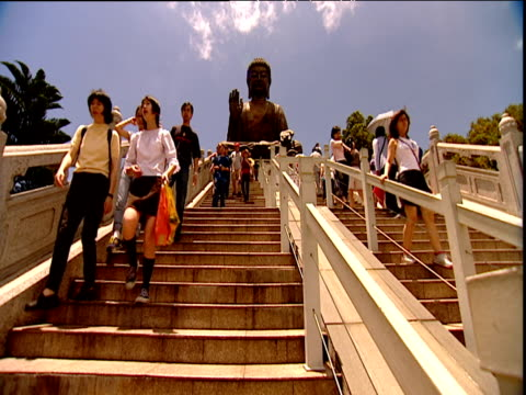 worshippers and tourists on steps up to huge buddha statue lantau island - sonnenschirm stock-videos und b-roll-filmmaterial