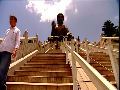 stockvideo's en b-roll-footage met worshippers and tourists on steps up to huge buddha statue lantau island - bedevaart