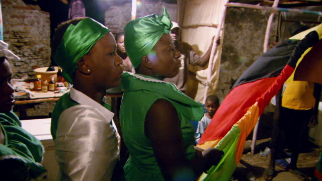 Worshippers dressed in green process around a hounfour during a Haitian Vodou ceremony, Haiti.