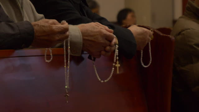 worshippers holding rosary beads in a catholic church - cristianesimo video stock e b–roll