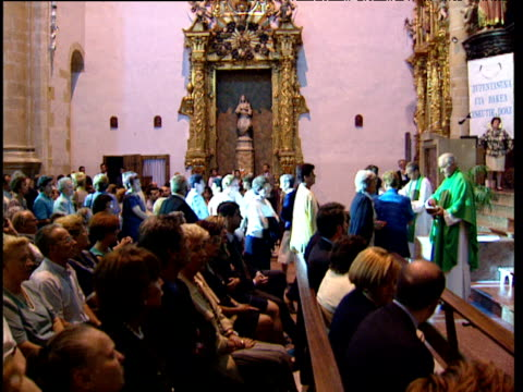 Worshippers queue to receive consecrated bread from priests during Mass in Catholic church Basque Country Spain