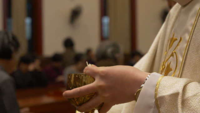 vídeos de stock e filmes b-roll de worshippers receiving communion in a catholic church - padre