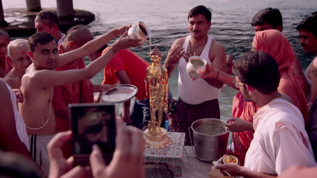 worshippers wash a hindu murti on the banks of the upper ganges, rishikesh, uttarakhand, india. - traditional clothing stock videos & royalty-free footage