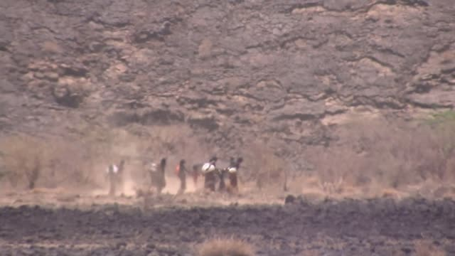 afar province ext long shot of group of women walking through parched desert landscape see through heat haze - heat haze stock videos & royalty-free footage