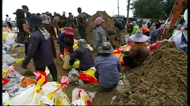 worst floods for half a century; people filling sandbags on banks of chao praya river sukhbhand paribatra interview sot - 緊急用具点の映像素材/bロール