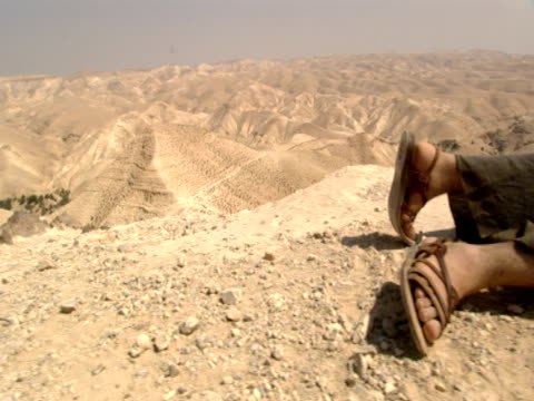 a wounded man lies on the barren desert in the parable of the good samaritan - religious illustration stock videos and b-roll footage
