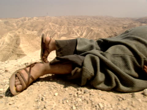 a wounded man lies on the ground in the parable of the good samaritan - historische kleidung traditionelle kleidung stock-videos und b-roll-filmmaterial