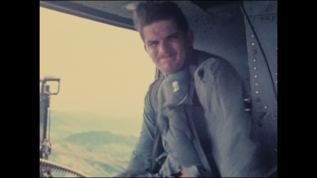 wounded north vietnamese prisoner in a huey heading to an american base. close-up of his face and american soldiers watching. - injured video stock e b–roll