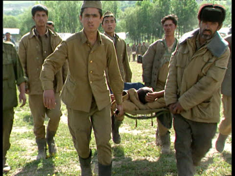 wounded soldier is carried on stretcher during tajikistan civil war tajikistan 1992 - 担架点の映像素材/bロール