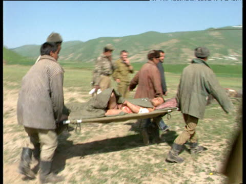 wounded soldier is carried on stretcher towards first aid helicopter during tajikistan civil war tajikistan 1992 - 担架点の映像素材/bロール