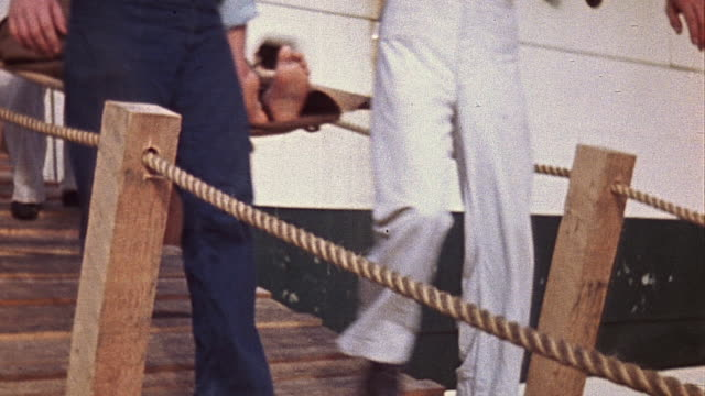 wounded soldier wearing arm and body cast and other injured soldiers on stretchers being carried by u.s. navy sailors down gangway of uss samaritan... - 硫黄島の戦い点の映像素材/bロール