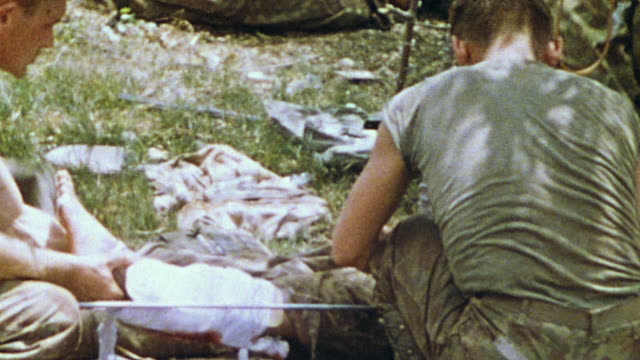 stockvideo's en b-roll-footage met wounded soldiers both stretcher cases and walking casualties undergoing triage at field hospital and being loaded into truck for transport / saipan... - triage