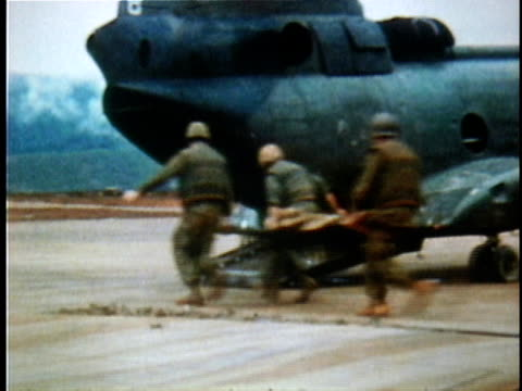 vídeos y material grabado en eventos de stock de wounded us soldiers on stretchers being loaded aboard transport plane during the tet offensive / vietnam - 1968