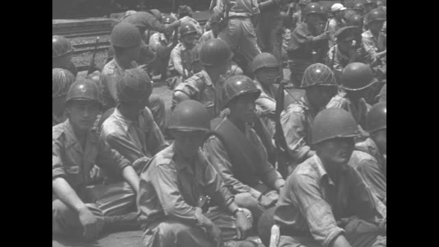 Wounded US soldiers on stretchers on ground during Korean War / close up of wounded US soldier / South Korean soldiers seated on the ground receiving...
