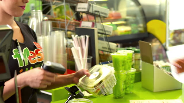 MS PAN wrap sandwich in plastic container handed to cashier at retail counter as cashier girl is about to process transaction