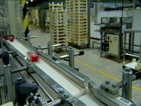 Wrapped chocolate bars travel along conveyer belt at speed as factory worker passes
