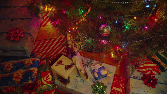 close up pan wrapped gifts under decorated christmas tree with colored lights - christmas gift stock videos & royalty-free footage