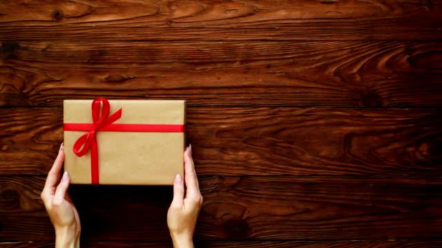 verpackte girt box erschien über hölzerne flache lay - eingewickelt stock-videos und b-roll-filmmaterial