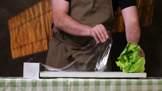 wrapping a salad crop in a cling film. - polyethylene stock videos and b-roll footage
