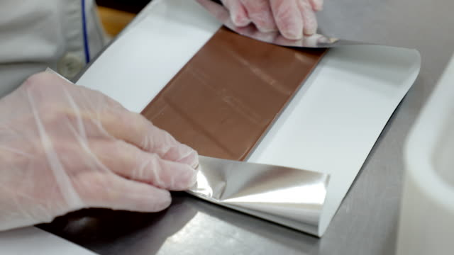 wrapping chocolate in aluminum foil - food processing plant stock videos & royalty-free footage