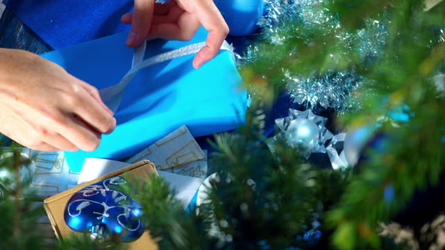 wrapping christmas presents in blue and silver - christmas gift stock videos & royalty-free footage