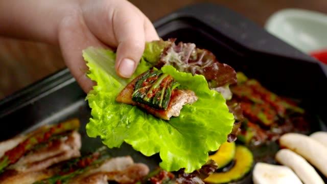 vídeos y material grabado en eventos de stock de wrapping pork belley in lettuce leaves with gat (leaf mustard) kimchi (popular traditional side dish in korea) and garlic - vegetal con hoja