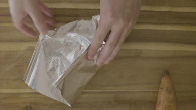 焼き付け用スズ箔でサツマイモを包む - サツマイモ点の映像素材/bロール